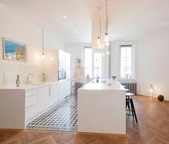 offene weiße küche mit fließenboden und eichen