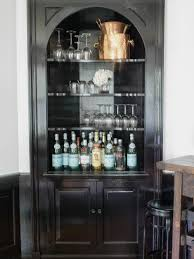 tall black wooden corner liquor cabinet with doors and arched