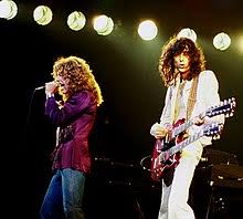 A Colour Photograph Of Robert Plant With Microphone And Jimmy Page Double Necked Guitar