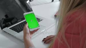 Woman Using Her Smartphone With Green Screen In Table Scrolling News