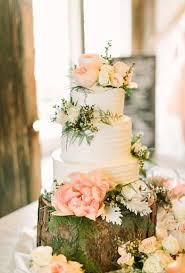A Three Tiered White Wedding Cake Covered In Blush Blooms By Virginias Cakes