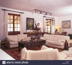 cremefarbene sofas und dunkles holz couchtisch in weißen