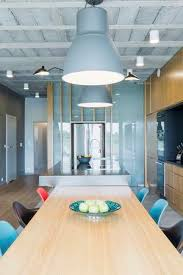 industriedesign inter mit einem esstisch aus holz bunte stühle und dekorative beleuchtung
