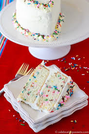 A slice of two layer sprinkle birthday cake on a white plate