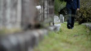 Elderly Man Walking Through Cemetery Front View