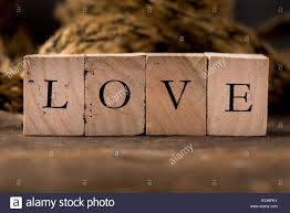 Stamping Blocks With The Word LOVE Spelled Out Set On Rustic Wood