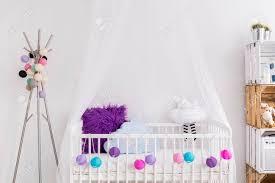 weißes mädchen wiege baby mit bunten kissen und bälle in der geräumigen weißen schlafzimmer