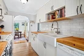 Galley Style Kitchen With White Cabinets Wood Floors