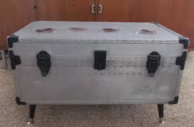old silver metal trunk coffee table with wooden legs on brown rugs