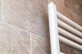 nahaufnahme weißen bad heizung an wand mit fliesen badezimmer hydraulische ausrüstung
