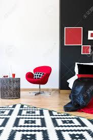 schwarz weiß gemusterter teppich im raffinierten schlafzimmer mit roten möbeln und metalltisch