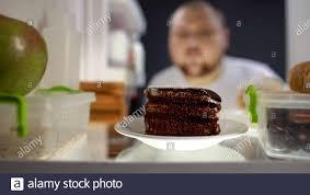 übergroße mann unter stück kuchen aus dem kühlschrank in der