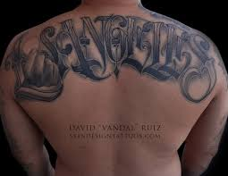 In This Upper Back Los Angeles Script Tattoo There Is A Hand Holding Up The Moon For O