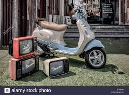 Vespa LX 125 Scooter On Display With Vintage 60s Style TV Sets