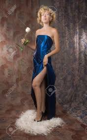 woman in a long dark blue dress with a white rose stock photo