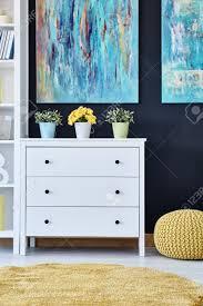 weiß kommode im modernen wohnzimmer mit gemälden dekoriert