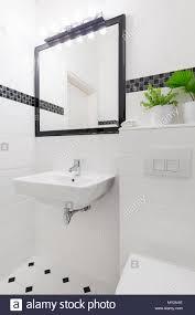 spiegel über dem waschbecken in weiß und schwarz bad