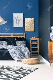 anspruchsvolles schlafzimmer mit eleganten blauen wänden teppich hocker und poster