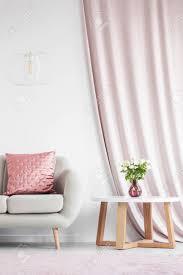 weiße le über beige sofa mit rosa kissen im weißen wohnzimmer interieur mit rosa vorhang