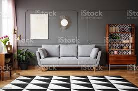 schwarz weiß teppich mit geometrischem muster auf dem boden im dunklen wohnzimmer interieur mit grauen sofa vintage schrank mit büchern und