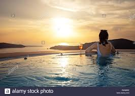 100 Infinity Swimming Woman Relaxing At The Edge Of Infinity Swimming Pool At Sunset Stock