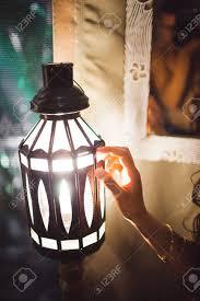 frauenhand berühren zart eine laterne in der dunkelkammer romantische nachtatmosphäre im badezimmer