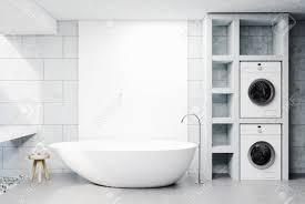 modernes badezimmer interieur mit betonwänden und boden ein waschbecken eine weiße wanne und zwei waschmaschinen ein stuhl mit gerollten