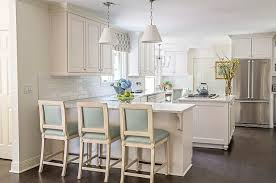 kitchen peninsula with blue leather counter stools and white