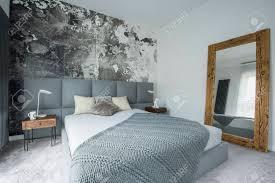 spiegel im holzrahmen im modernen schlafzimmerinnenraum mit bett neben einem hölzernen schrank mit le