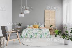 sessel mit hahnentrittmuster in echtes foto hellen schlafzimmer innenraum mit zwei len doppelbett mit grünen blättern und kissen und monstera