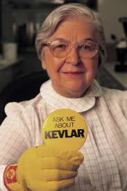 Inventor Stephanie Kwolek Wearing Yellow Kevlar Glove And Holding Up Button That Reads Ask