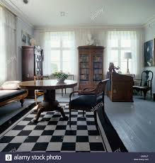 antiker tisch und stühle auf schwarz weiß teppich im