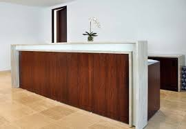This Reception Desk Features Quartered Walnut Wood A Saddle Counter Made Of Travertine And Is Accented With White Back Painted Glass