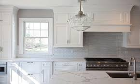 white kitchen with mini brick marble tiles and clear glass