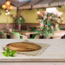 Round board on kitchen table over cafe interior background — Stock