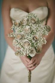 A bouquet made out of book page roses laced with baby s breath