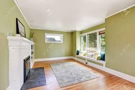 wohnzimmer interior design der handwerker zu hause mit weißen gemauerten kamin einbauregalen fensterplatz mit kissen hellgrünen wänden und