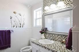 elegantes land badezimmer mit lila handtücher
