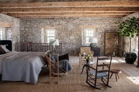 schlafzimmer mit steinmauern und sichtbalken im steinhaus