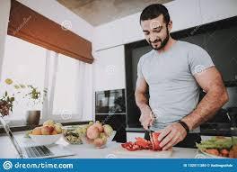 athletische mann stände in der küche kochen des konzeptes