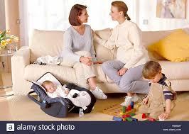 portrait 2 frauen sitzen mit ihren kleinen kindern im
