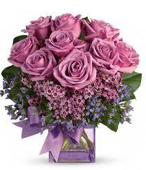 Purple roses in square glass vase