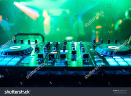 DJ Booth At Night Club Party For Music Mixing With Green Blurred Background