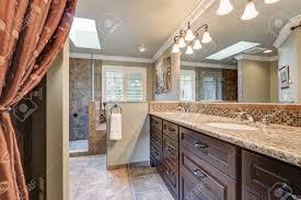 frisch renovierte badezimmer mit wunderschönen doppelwaschbecken waschtisch mit dunklen schränken granit und mosaik backsplash und oberlicht über