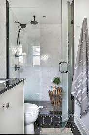 black hex shower floor tiles with gray marble herringbone wall