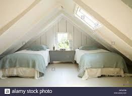 zwei einzelbetten in zimmer im dachgeschoss mit dachschrä