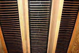 stapling underfloor heating between floor joists to heat a room above