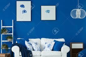 sofa mit blauen und weißen kissen im gemütlichen wohnzimmer