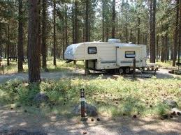 RV Trailer Parked In Pine Forest Campground Although The