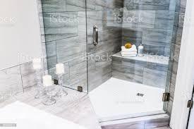 nahaufnahme staging stein grau gekachelte badezimmer marmorarbeitsplatte in vorbildliches haus wohnung oder haus mit kerzen handtücher hocker